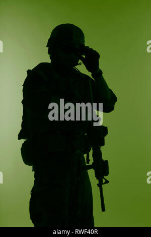 Silhouette of a U.S. Marine Corps Marsoc raider with weapon, green background. - Stock Photo