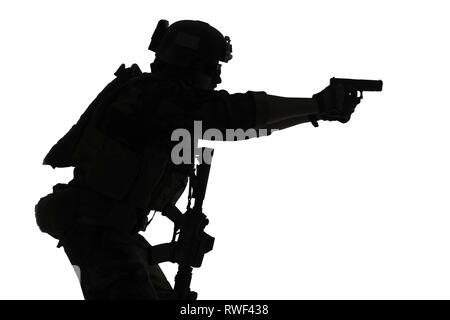 Silhouette of a U.S. Marine Corps Marsoc raider aiming pistol, white background. - Stock Photo
