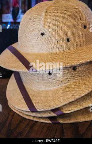 34049c5f9cf8b old cork helmet  stack of natural fiber woven pith helmets for sale on a  wood table - Stock Photo