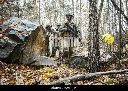 Norwegian Rapid reaction special forces FSK soldiers patrolling in the forest trees. - Stock Photo