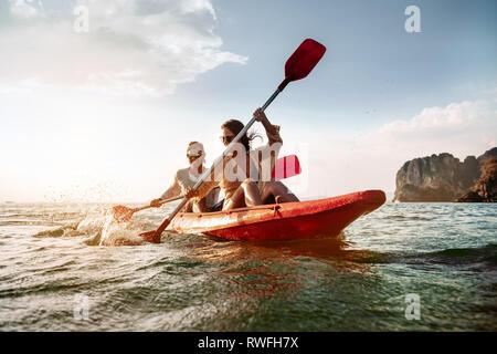 Happy couple walks by sea kayak or canoe at tropical bay - Stock Photo