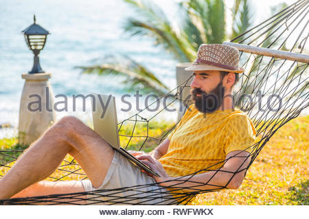 Man working with a laptop, on a hammock in the beach. - Stock Photo