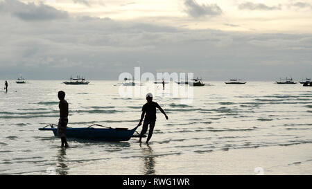 Small fishing boats dragged to beach by two men - silhouettes on Boracay Island, Panay - Philippines - Stock Photo