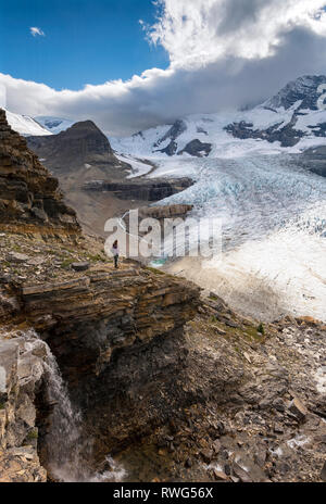 A young woman stops to take in the view on the trail to Snowbird pass, overlooking the Robson glacier, Mt. Robson Provincial Park, British Columbia, T - Stock Photo