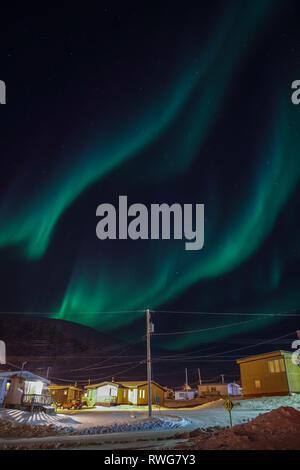 Aurora Borealis dancing over homes in Pangnirtung - Stock Photo