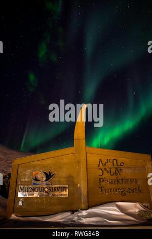 Aurora Borealis dance over the camping area behind Pangnirtung - Stock Photo