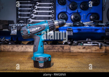 Close-up of a blue modern manual screwdriver on a metal table against the background of a toolbox in a workshop. Close-up Carpenter's Tool Kit - Stock Photo