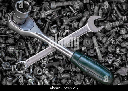 Flat Lay metal wrenches and ratchet of different sizes lie on the background of various metal cogs, screws and nails, top view. Close-up Carpenter's T - Stock Photo