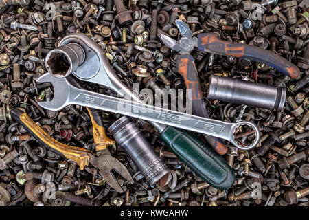Flat Lay metal wrenches, ratchet, pliers, interchangeable tool heads of different sizes lie on the background of various metal cogs, screws and nails, - Stock Photo