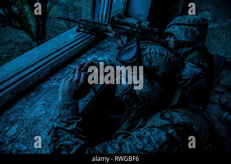 Sniper team with large caliber sniper rifle hiding in a ruined urban building at night. - Stock Photo