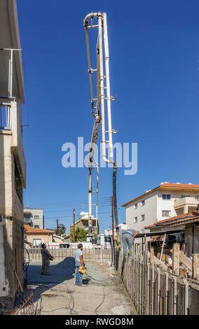 Limassol, Cyprus - April 3, 2018: Delivery of concrete to make a shutter prepared wall.  Long telescopic arm reaching high into the sky to pump cement - Stock Photo