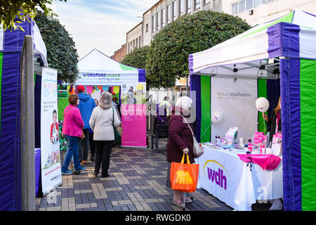 People shopping at busy Wakefield Food, Drink & Rhubarb Festival 2019, visiting colourful market trade tents or stalls - West Yorkshire, England, UK - Stock Photo