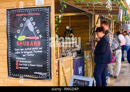 People shopping at busy Wakefield Food, Drink & Rhubarb Festival 2019 visiting market trade stall selling bottles of gin - West Yorkshire, England, UK - Stock Photo