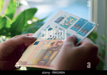 In women's hands a paper envelope with postage stamps of Hong Kong and Euro banknotes - Stock Photo