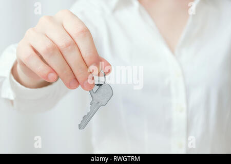 Caucasian girl in white shirt holds key in hand. Close-up. - Stock Photo
