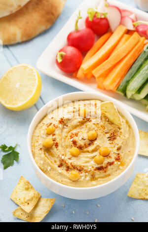 Hummus and variety of vegetable sticks and chips. Healthy snacks. - Stock Photo