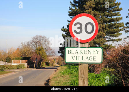A 30 mph sign and village name on the Langham Road entering the North Norfolk village of Blakeney, Norfolk, England, United Kingdom, Europe. - Stock Photo