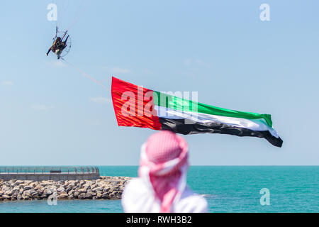 A local Emirati man seen looking on as a paraglider with the UAE national flag flies over Al Marjan Island, during the event. The Special Olympics World Games 2019 will be hosted in Abu Dhabi, United Arab Emirates in March 2019 for the first time in the Middle East and North Africa since the movement's founding over 50 years ago. The final stage of the Special Olympics Law Enforcement Torch Run was held on Al Marjan Island, Ras Al Khaimah. The event was celebrated with traditional Emirati music and dances. The CEO of Marjan and Master Developer of Ras Al Khaimah, Mr Abdulla Al Abdouli opened t - Stock Photo
