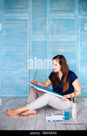 Portrait of female painter sitting on floor near wall after painting. - Stock Photo