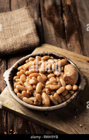 closeup of an earthenware bowl with a cassoulet de Castelnaudary, a typical bean stew from Occitanie, in France, on a rustic wooden table - Stock Photo