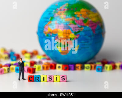 miniature figure businessman in dark blue suit standing backside of colorful of CRISIS alphabet and globe in the background and thinking of the crisis - Stock Photo