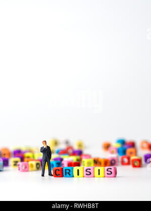 miniature figure businessman in dark blue suit standing backside of colorful of CRISIS alphabet and thinking of the crisis will come. - Stock Photo