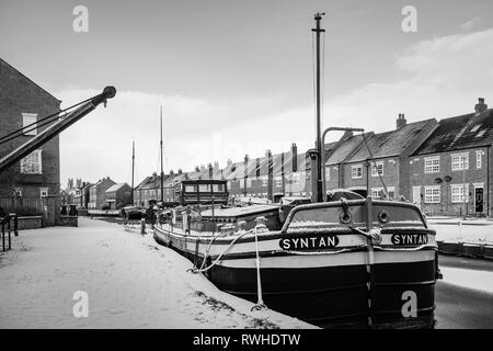 Vintage barges moored along the frozen beck (canal) and covered in snow flanked by town houses in Beverley, Yorkshire, UK. - Stock Photo