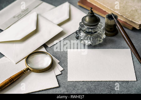 Set of vintage writing stationery items, wooden pen, inkwell, magnifier and envelopes, letters closeup. - Stock Photo