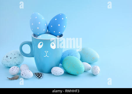 Easter eggs and a cup in the form of a rabbit on a blue background. Easter card with empty space for text - Stock Photo