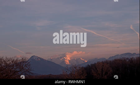 The highest mountain in Europe turns pink in the sunset as the clouds gather around the high snowy alpine peak. - Stock Photo