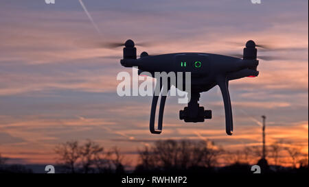 A drone hovers in flight in front of a sunset background. The drone is stationary hovering above the ground as the sunsets in the distance. - Stock Photo
