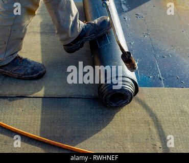 Worker preparing part of bitumen roofing felt roll for melting by gas heater torch flame. On the back of the sheath there is the stamp  'Made in Italy - Stock Photo