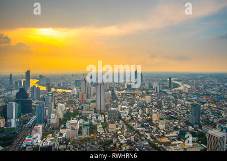 Orange sunset sky at skyline over Bangkok city central business downtown with curved view of Chao Phraya River. Bangkok - THAILAND