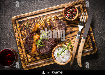 Grilled beef steak medium on wooden cutting board. - Stock Photo