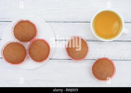 Biscuit muffins on a white plate and a cup of green tea. On a white wooden background. - Stock Photo