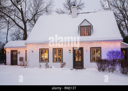 Old circa 1886 white with beige and brown trim Canadiana cottage style home facade with illuminated Christmas lights and decorations at dusk in winter - Stock Photo