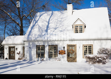 Old circa 1886 white with beige and brown trim Canadiana cottage style home facade with Christmas decorations in winter, Quebec, Canada - Stock Photo