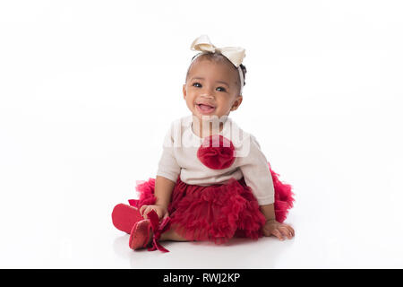 A smiling six month old baby girl wearing a red tutu. She is sitting on a white, seamless background. - Stock Photo