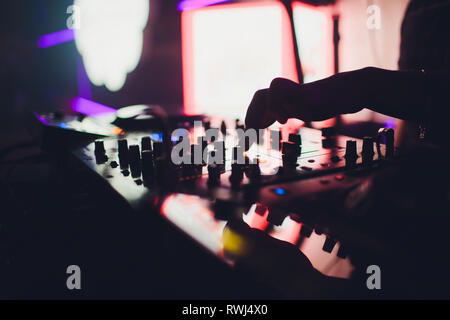 DJ controls a remote at a club party - Stock Photo