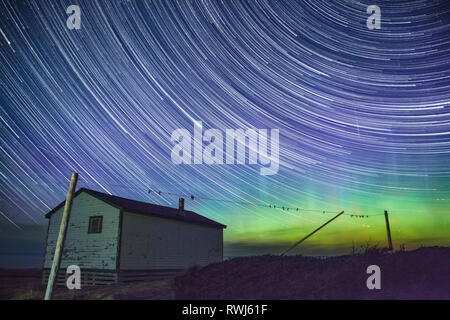 Star Trails & Northern Lights Aurora Borealis over Broom Point, Gros Morne National Park, Newfoundland and Labrador - Stock Photo