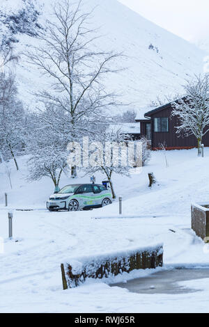 BMW Electric car being charged at electric car charging station point in snow covered car park by Clachaig Inn, Glencoe, Highlands, Scotland in Winter - Stock Photo