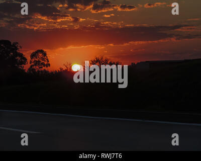 A beautiful view of a reddish sunset with a dark road in the foreground and a black background - Stock Photo