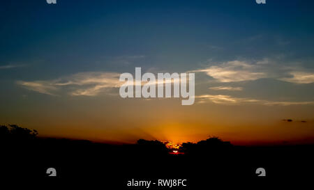 A landscape view of a beautiful sunset with a sky with graduated colors from black in the top, blue in the middle and orange in the base - Stock Photo