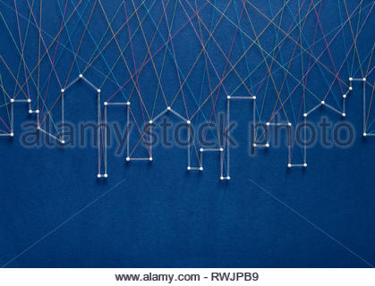 Urban connection concept. Network of pins and threads in the shape of a city skyline symbolising urban diversity and communication. - Stock Photo