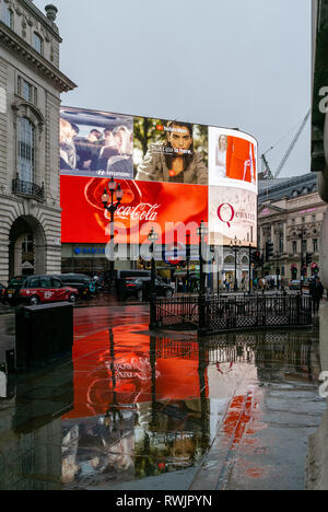 Piccadilly Circus, London in the rain showing the reflections on the pavements - Stock Photo