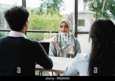 veiled women interviewed as new employees by two human resources departments - Stock Photo