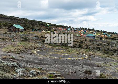 Shira Cave Camp, Kilimanjaro, Tanzania - February 18 2019: View across the helipad and campsite of the Shira Cave Camp on Kilimanjaro. - Stock Photo