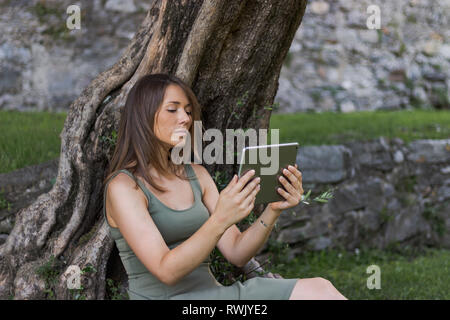 Woman reading tablet and enjoy rest in a park under tree. Castle of Bellinzona, Switzerland - Stock Photo