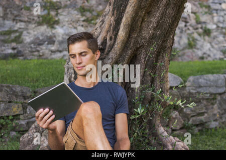 Man reading tablet and enjoy rest in a park under tree. Castle of Bellinzona, Switzerland - Stock Photo