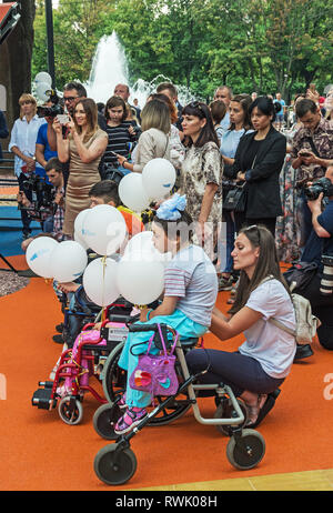 Dnipro, Ukraine - June 27, 2018: Cute kids in wheelchairs at inclusive park for children with special needs - Stock Photo